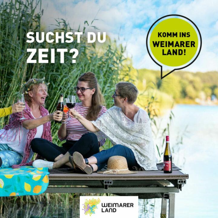 Mädels sitzen zusammen auf einem Steg am Stausee Hohenfelden, trinken und lachen zusammen